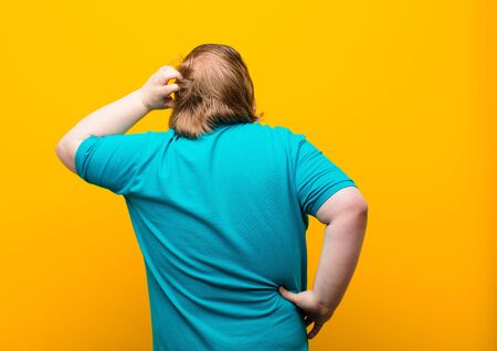 young big size man feeling clueless and confused, thinking a solution, with hand on hip and other on head, rear view against orange wall