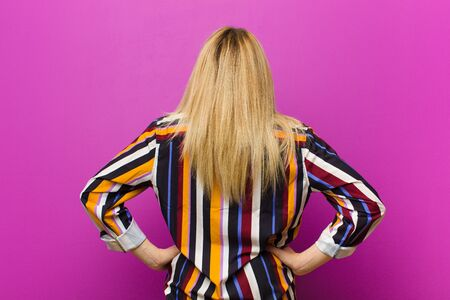 young blonde woman feeling confused or full or doubts and questions, wondering, with hands on hips, rear view against purple wall Standard-Bild