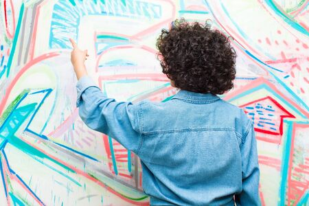young pretty afro woman standing and pointing to object on copy space, rear view against graffiti wall