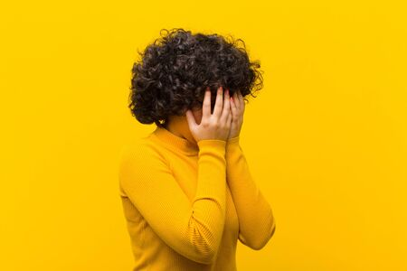young pretty afro woman covering eyes with hands with a sad, frustrated look of despair, crying, side view