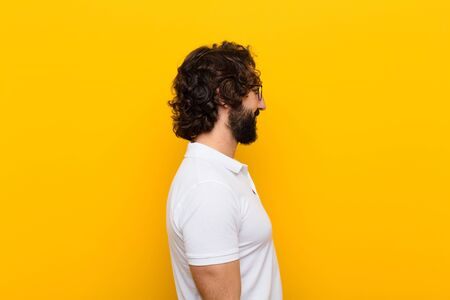 young crazy man on profile view looking to copy space ahead, thinking, imagining or daydreaming against yellow wall