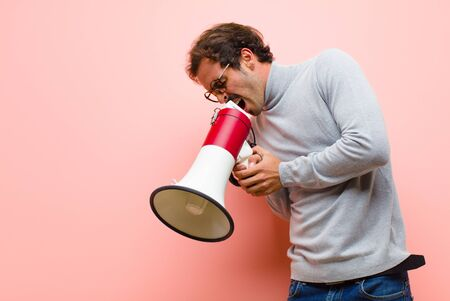 young handsome man with a megaphone against pink flat wall