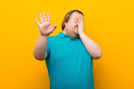 young big size man covering face with hand and putting other hand up front to stop camera, refusing photos or pictures against orange wall
