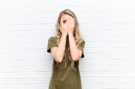 young blonde woman covering face with hands, peeking between fingers with surprised expression and looking to the side against brick wall background Standard-Bild