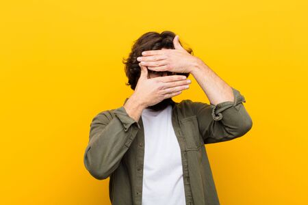 young crazy man covering face with both hands saying no to the camera! refusing pictures or forbidding photos against yellow wall