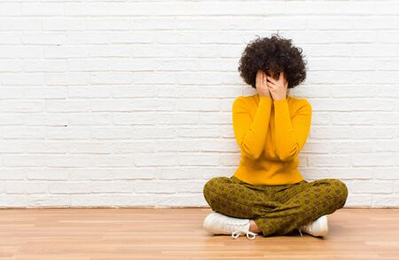 young pretty afro woman covering face with hands, peeking between fingers with surprised expression and looking to the side sitting on the floor