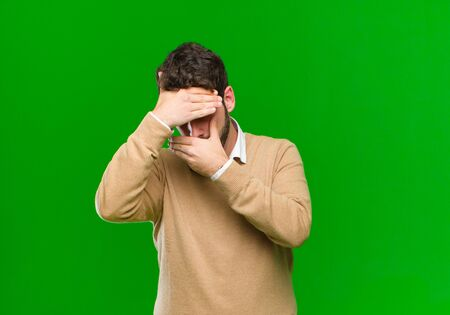 young businessman covering face with both hands saying no to the camera! refusing pictures or forbidding photos against green background