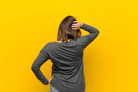 latin american woman thinking or doubting, scratching head, feeling puzzled and confused, back or rear view isolated against yellow wall