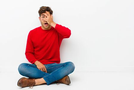 young handsome man looking shocked, scared or terrified, covering face with hand and peeking between fingers sitting on the floor Standard-Bild