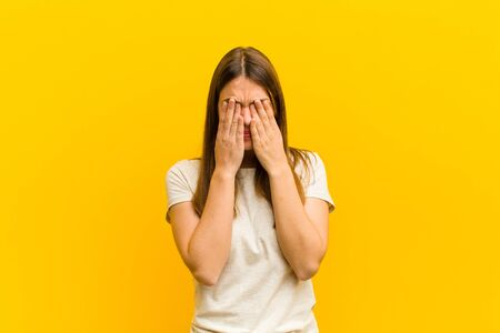 young pretty woman feeling sad, frustrated, nervous and depressed, covering face with both hands, crying against orange background