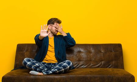 young man wearing pajamas covering face with hand and putting other hand up front to stop camera, refusing photos or pictures . sitting on a sofa