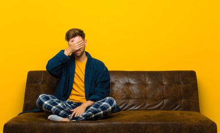 young man wearing pajamas looking stressed, ashamed or upset, with a headache, covering face with hand . sitting on a sofa