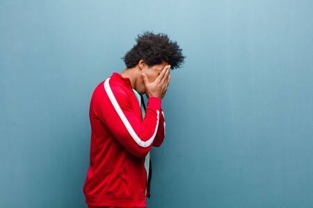 young black sports man covering eyes with hands with a sad, frustrated look of despair, crying, side view against grunge wall