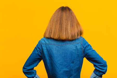 young pretty woman feeling confused or full or doubts and questions, wondering, with hands on hips, rear view against yellow background