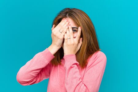 young pretty woman covering face with hands, peeking between fingers with surprised expression and looking to the side against blue background