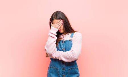 young  pretty woman looking stressed, ashamed or upset, with a headache, covering face with hand against pink background. Standard-Bild