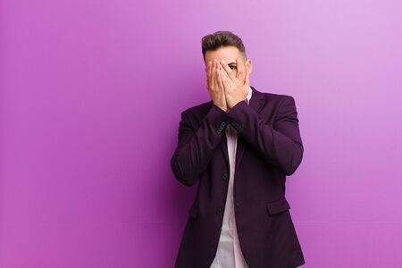 young hispanic man feeling scared or embarrassed, peeking or spying with eyes half-covered with hands