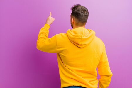 young hispanic man with casual look against purple background