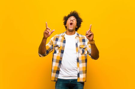 young black man looking shocked, amazed and open mouthed, pointing upwards with both hands to copy space against orange wall Standard-Bild