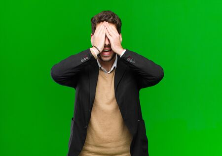 young businessman smiling and feeling happy, covering eyes with both hands and waiting for unbelievable surprise against green background