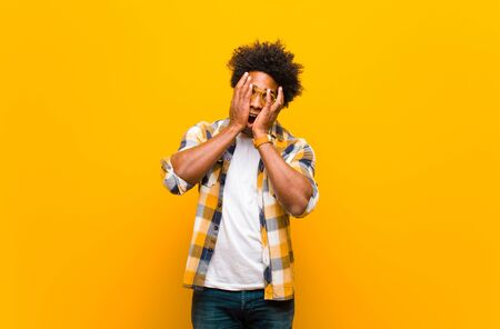 young black man feeling scared or embarrassed, peeking or spying with eyes half-covered with hands against orange wall Standard-Bild