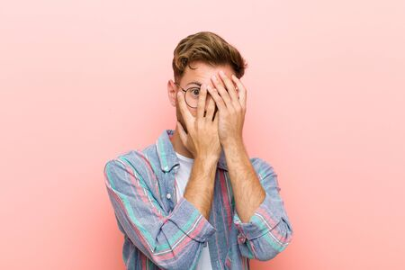 young man feeling scared or embarrassed, peeking or spying with eyes half-covered with hands against pink background Standard-Bild