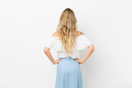 young blonde woman feeling confused or full or doubts and questions, wondering, with hands on hips, rear view against white wall
