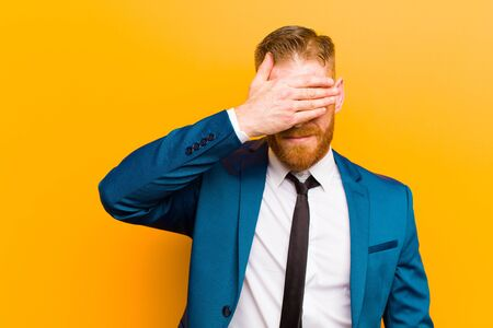 young red head businessman covering eyes with one hand feeling scared or anxious, wondering or blindly waiting for a surprise against orange background Standard-Bild
