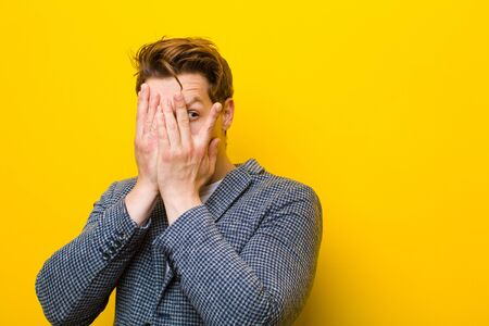 young red head man covering face with hands, peeking between fingers with surprised expression and looking to the side against orange background Standard-Bild