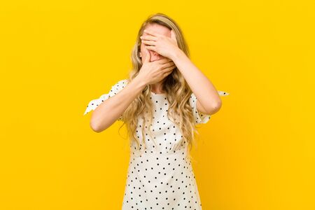 young blonde woman covering face with both hands saying no to the camera! refusing pictures or forbidding photos against yellow wall Standard-Bild