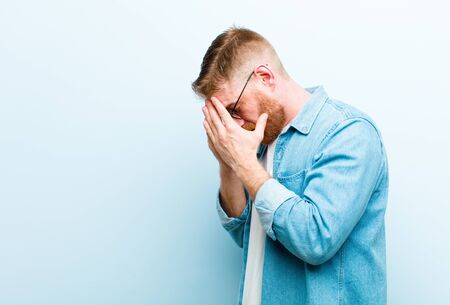 young red head man covering eyes with hands with a sad, frustrated look of despair, crying, side view against soft blue background Standard-Bild