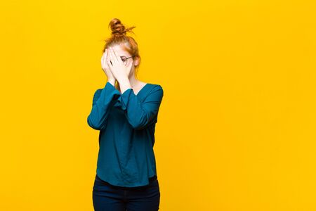 young red head woman covering face with hands, peeking between fingers with surprised expression and looking to the side against orange wall Standard-Bild - 135892614