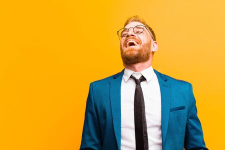 young red head businessman screaming furiously, shouting aggressively, looking stressed and angry against orange background Standard-Bild - 135892978