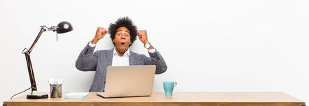 young black businessman celebrating an unbelievable success like a winner, looking excited and happy saying take that! on a desk Standard-Bild - 135893000