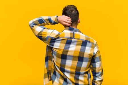 young hispanic man thinking or doubting, scratching head, feeling puzzled and confused, back or rear view against orange wall