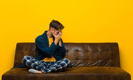 young man wearing pajamas covering eyes with hands with a sad, frustrated look of despair, crying, side view . sitting on a sofa Standard-Bild - 135946609