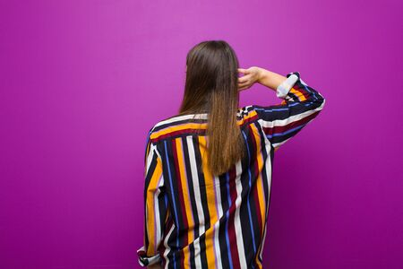 young pretty woman thinking or doubting, scratching head, feeling puzzled and confused, back or rear view against purple background Standard-Bild - 135946740
