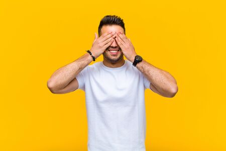 young hispanic man smiling and feeling happy, covering eyes with both hands and waiting for unbelievable surprise against orange wall Standard-Bild - 135946932