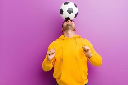 young hispanic man with a soccer ball against purple background Standard-Bild - 135947108