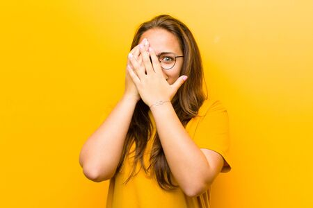 young pretty woman feeling scared or embarrassed, peeking or spying with eyes half-covered with hands against orange background Standard-Bild - 135946924
