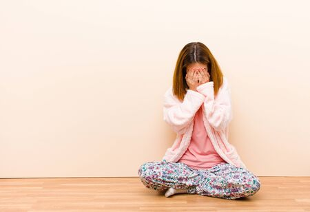 young woman wearing pajamas sitting at home feeling sad, frustrated, nervous and depressed, covering face with both hands, crying Standard-Bild - 135946882