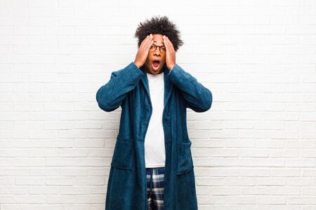 young black man wearing pajamas with gown looking unpleasantly shocked, scared or worried, mouth wide open and covering both ears with hands against brick wall