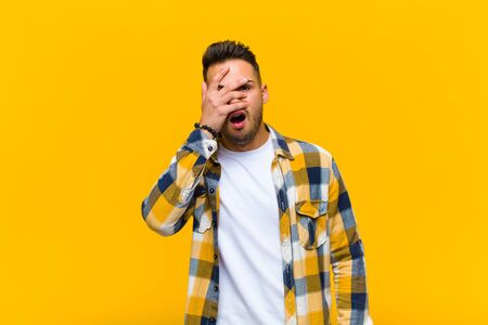 young hispanic man looking shocked, scared or terrified, covering face with hand and peeking between fingers against orange wall Standard-Bild - 135946654