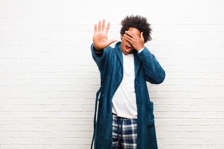 young black man wearing pajamas with gown covering face with hand and putting other hand up front to stop camera, refusing photos or pictures against brick wall Standard-Bild - 135946678