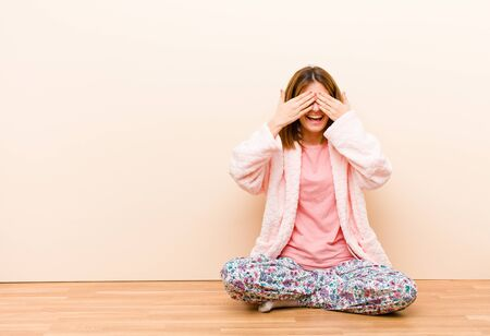 young woman wearing pajamas sitting at home smiling and feeling happy, covering eyes with both hands and waiting for unbelievable surprise Standard-Bild - 135947189