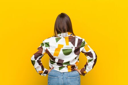 latin american woman feeling confused or full or doubts and questions, wondering, with hands on hips, rear view isolated against yellow wall Standard-Bild - 135946970
