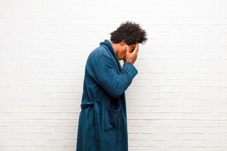 young black man wearing pajamas with gown covering eyes with hands with a sad, frustrated look of despair, crying, side view against brick wall Standard-Bild - 135947231