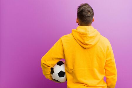 young hispanic man with a soccer ball against purple background Standard-Bild - 135947253