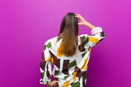 young pretty woman feeling clueless and confused, thinking a solution, with hand on hip and other on head, rear view against purple background