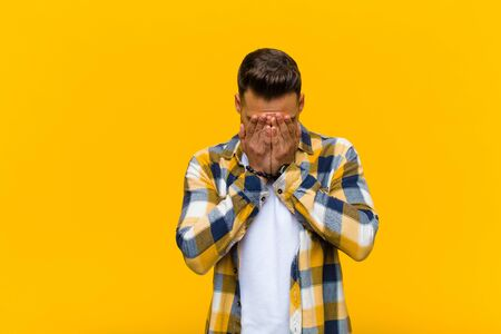 young hispanic man feeling sad, frustrated, nervous and depressed, covering face with both hands, crying against orange wall Standard-Bild - 135947230